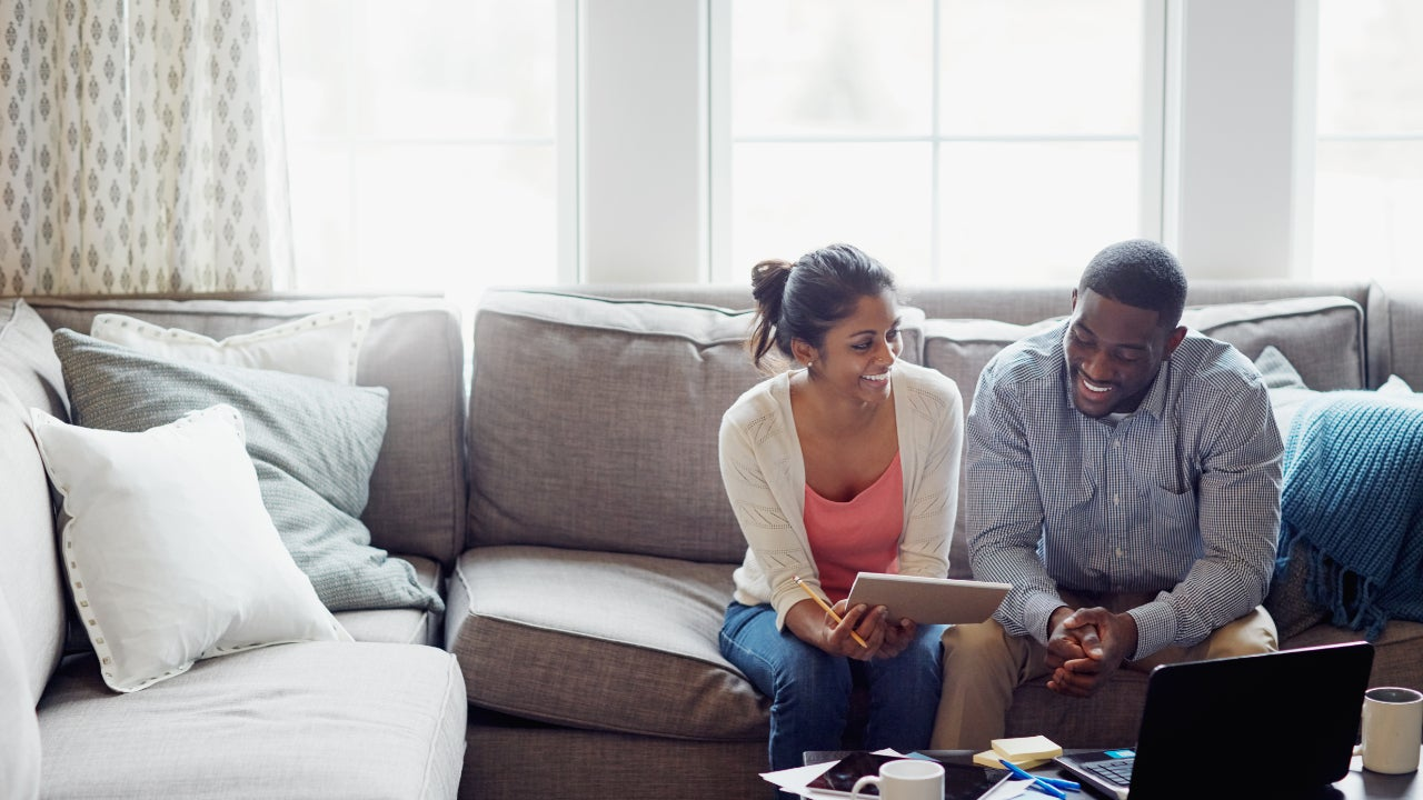 A young couple going through paperwork together on the sofa at home