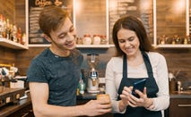 Young barristas smile as they look together at a smartphone