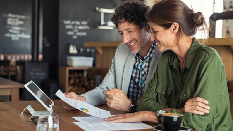 Middle-aged couple filing taxes on laptop