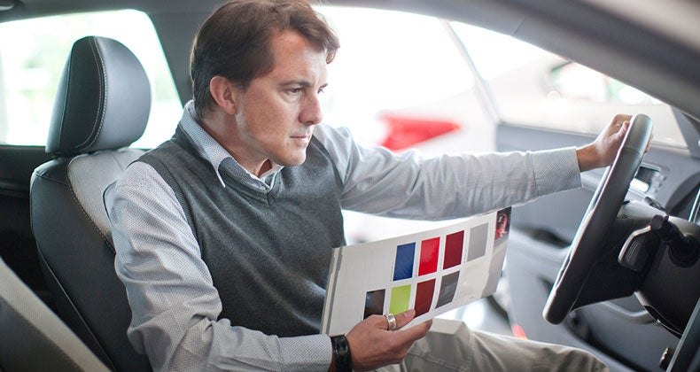 Man holding sales packet inspecting car in front seat   Zero Creatives/Getty Images
