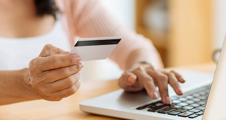 Woman entering her credit card info © iStock