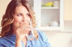 Woman sipping a glass of water © iStock.com/elenaleonova
