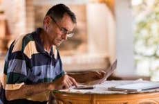 Older man doing paperwork   skynesher/Getty Images