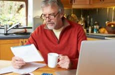 Mature man in red fleece pullover going over finances in kitchen   iStock.com/omgimages