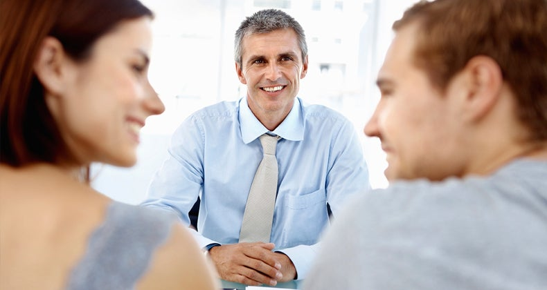 Banker smiling at couple at his desk © iStock