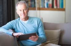 Senior male in light blue sweater browsing tablet   Alistair Berg/DigitalVision/Getty Images