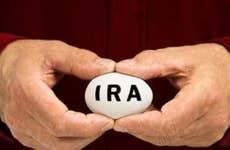 Man in red shirt holding IRA egg © Bryan Sikora/Shutterstock.com