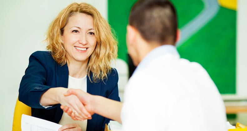 Businesswoman shaking man's hand | iStock.com/vgajic