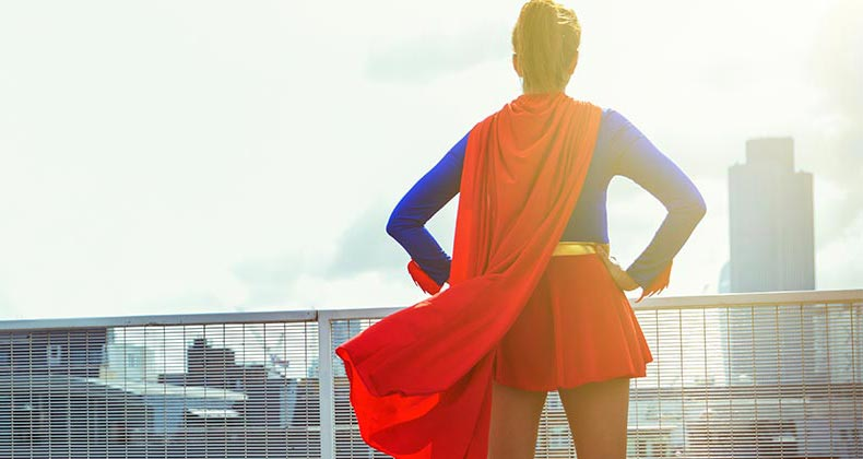 Woman standing on rooftop wearing a superhero outfit | Robert Daly/Getty Images