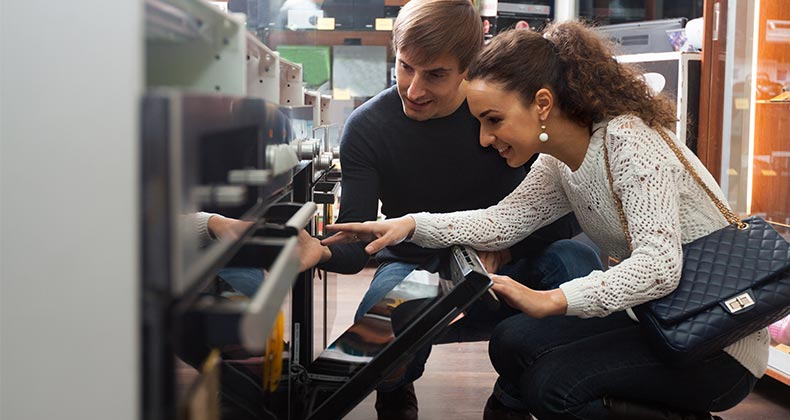 Couple shopping for stoves   Caftor/Shutterstock.com