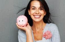 Smiling young woman holding piggy bank © Yuri Arcurs - Fotolia.com