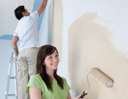 Young couple painting the walls