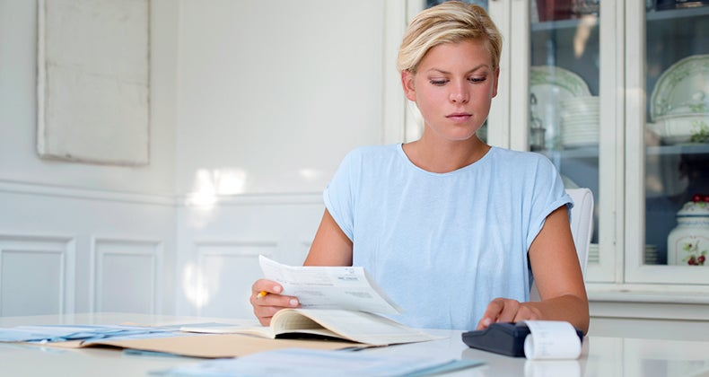 Blond woman at table calculating bills © iStock