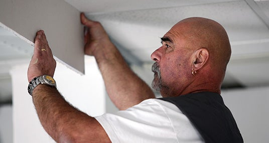 Tradesman installing drywall © auremar/Shutterstock.com