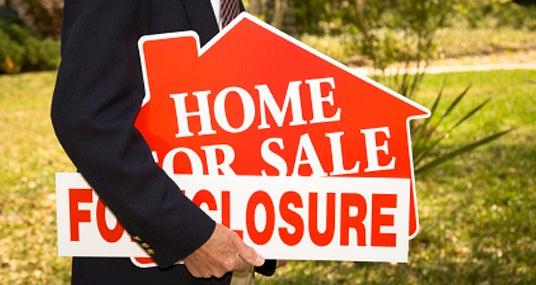 Foreclosure sign under arm © iStockPhoto.com