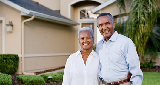 Happy couple standing outside their home © iStock