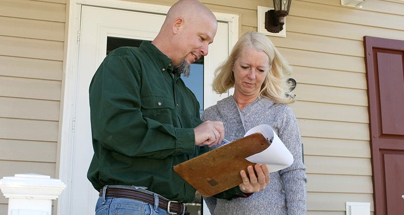 Man reviewing clipboard information with woman © iStock