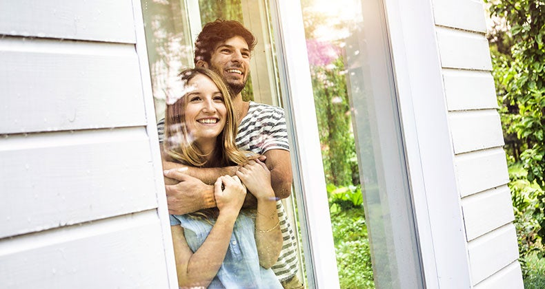 Homeowners looking out of their window | Matelly/Cultura/Getty Images