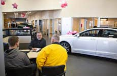 Two men sitting with car dealer, negotiating price
