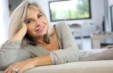 Mature woman relaxing on living room couch © goodluz/Shutterstock.com