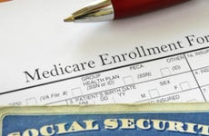 Medicare enrollment form and Social Security card © iStock