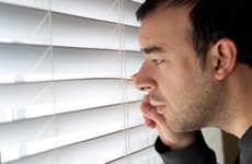 Man peeking through windowblinds © ARENA Creative/Shutterstock.com