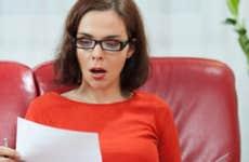 Shocked woman looking at document © bokan/Shutterstock.com