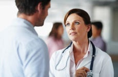 Doctor talking to man in hallway © iStock