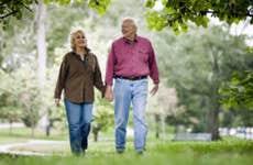 Senior couple walking under tree cover | Stevecoleimages/Vetta/Getty Images