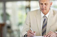 Businessman writing in notebook © iStock