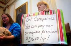 Woman holding sign protesting oil companies in Oklahoma State Capital   J Pat Carter/Getty Images
