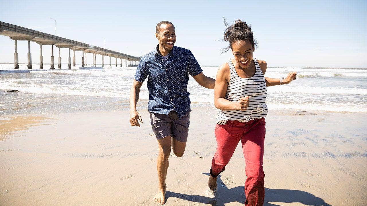 ビーチを走る若いカップル