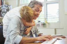Young son hugging dad working from home office   Paul Bradbury/Getty Images