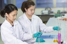 Two chemists measuring liquids | MeemiePhoto/Shutterstock.com