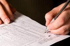 Man signing tax form © Mehmet Dilsiz - Fotolia.com