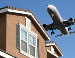 A passenger jet flying over a house
