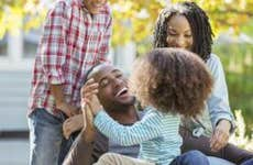 Young family laughing and hugging outdoors | Paul Bradbury/Getty Images
