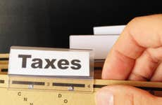 """Male hand holding folder with tab labeled """"Taxes"""" © gunnar3000 - Fotolia.com"""