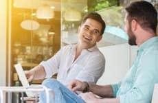 Two men sitting outside, laughing | Vasin Lee/Shutterstock.com