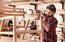 Man sanding down chair   mavo/Shutterstock.com