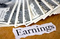 The word 'earnings' and $100 bills on the background
