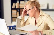 Woman slumping at her home office desk © iStock