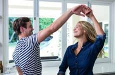 Young couple laughing and dancing together in kitchen | wavebreakmedia/Shutterstock.com