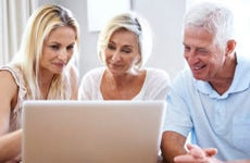 Adult daughter showing computer screen to senior parents © iStock