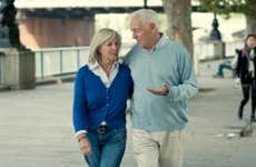 Older couple walking along bridge, talking   VisitBritain/Getty Images