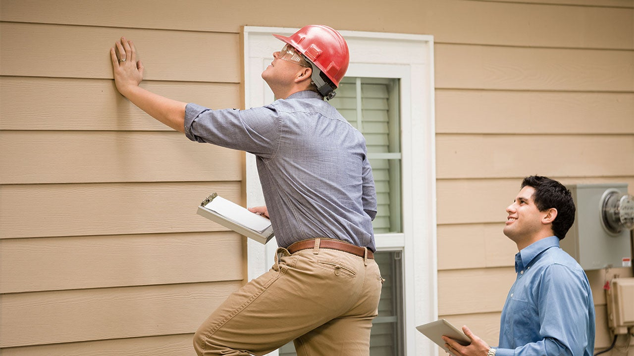 Two home appraisers examining a house