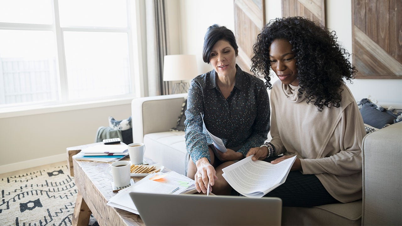 Two women look over paperwork and a computer