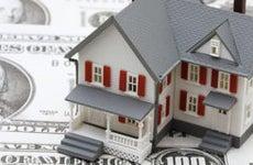 Toy house on money © karen roach/Shutterstock.com