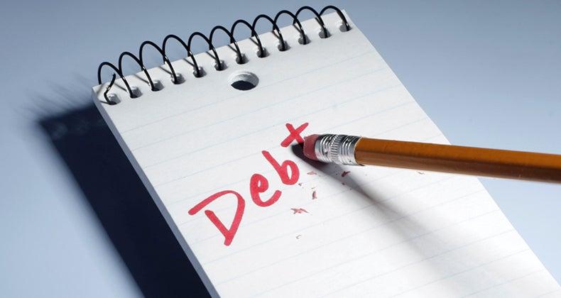 Pencil eraser erasing the word 'debt' on notebook © iStock