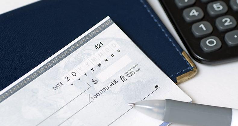 Checkbook, pen and a calculator © JJ Studio/Shutterstock.com